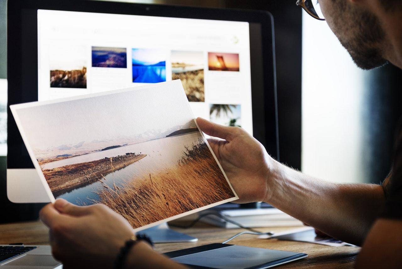férfi papírképeket nézeget számítógép előtt