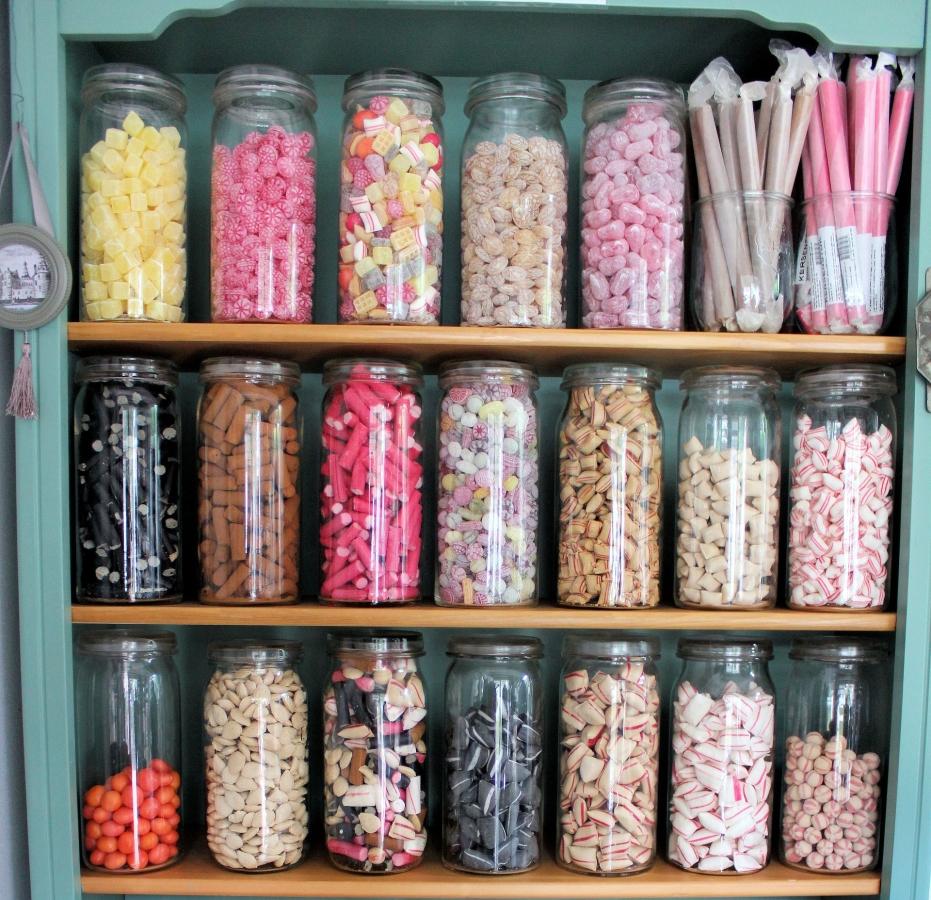 különböző cukorkák egy polcon üvegekben